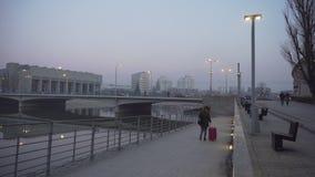 La muchacha con una maleta rosada camina en una orilla del río brumosa en Wroclaw almacen de metraje de vídeo