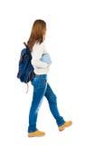 La muchacha con una mochila en el suyo detrás es una pila de libros Fotos de archivo libres de regalías