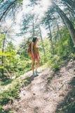 La muchacha con una mochila está caminando a través del bosque Foto de archivo