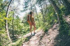 La muchacha con una mochila está caminando a través del bosque Fotografía de archivo