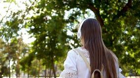 La muchacha con una mochila va a parquear en auriculares y escucha la música y las sonrisas, adolescente agitan feliz su mano en almacen de metraje de vídeo