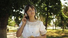 La muchacha con una mochila va a parquear en auriculares y escucha la m?sica y las sonrisas, adolescente agitan feliz su mano en almacen de video