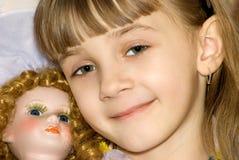 La muchacha con una muñeca Fotografía de archivo libre de regalías