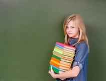 La muchacha con una pila reserva cerca de la pizarra verde vacía Fotos de archivo libres de regalías