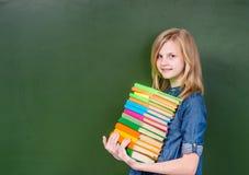 La muchacha con una pila reserva cerca de la pizarra verde vacía Fotografía de archivo