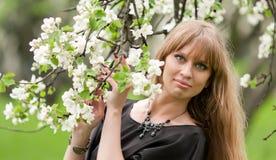 La muchacha con una ramificación de un manzana-árbol floreciente Fotos de archivo