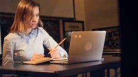 La muchacha con una taza de café antes del ordenador portátil resbalador Retrato 4K almacen de video