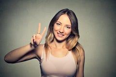 La muchacha con Victory Sign aisló en fondo gris de la pared Fotos de archivo libres de regalías
