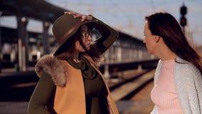 La muchacha con vidrios y un sombrero está en el ferrocarril y esperar el tren Detrás de su viene una muchacha y pide almacen de video