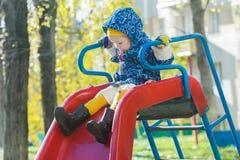 La muchacha concentrada en la chaqueta con capucha caliente que desliza abajo la diapositiva plástica roja del patio en el árbol  Foto de archivo