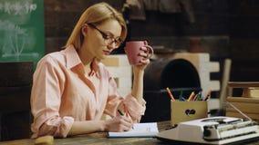 La muchacha concentrada lista inteligente linda está estudiando difícilmente en la clase, anotando la información necesaria a su  almacen de metraje de vídeo