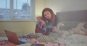 La muchacha concentrada primer en su dormitorio prepara un cuaderno para comenzar a jugar en una guitarra, ella muy está gozando  almacen de video