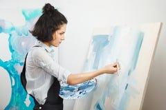 La muchacha concentrada se centró en proceso de arte-fabricación creativo en terapia del arte imagenes de archivo
