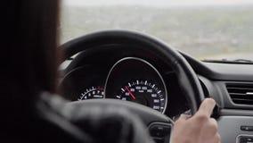 La muchacha conduc?a mientras que ca?a la lluvia La conducción en el camino en las fuertes lluvias debe ser prudente Fuertes lluv almacen de video