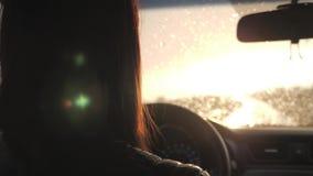La muchacha conduc?a mientras que ca?a la lluvia La conducci?n en el camino en las fuertes lluvias debe ser prudente Fuertes lluv almacen de video