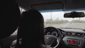 La muchacha conduc?a mientras que ca?a la lluvia La conducci?n en el camino en las fuertes lluvias debe ser prudente Fuertes lluv almacen de metraje de vídeo