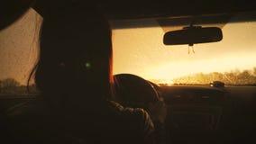 La muchacha conduc?a mientras que ca?a la lluvia La conducci?n en el camino en las fuertes lluvias debe ser prudente Fuertes lluv metrajes