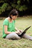 La muchacha conecta con el Internet en el parque Fotos de archivo libres de regalías