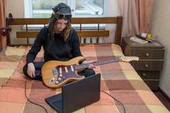 La muchacha conecta la guitarra eléctrica con el ordenador portátil que se sienta en la cama Fotos de archivo libres de regalías