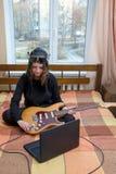 La muchacha conecta la guitarra eléctrica con el ordenador portátil que se sienta en la cama Fotos de archivo