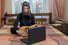 La muchacha conecta la guitarra eléctrica con el ordenador portátil que se sienta en t Imágenes de archivo libres de regalías