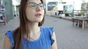 La muchacha confusa joven camina alrededor de la ciudad metrajes