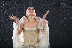La muchacha congela en lluvia y coge gotas Fotos de archivo libres de regalías
