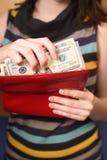 La muchacha consigue dólares de un monedero Fotos de archivo