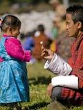 La muchacha consigue el caramelo de su padre en un festival Foto de archivo libre de regalías