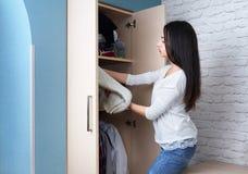 La muchacha consigue la ropa con el guardarropa Imagen de archivo libre de regalías