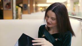 La muchacha consigue un regalo del bolso de papel en la alameda almacen de video