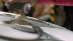 La muchacha consigue una pintura de un envase en una carrocería blanca almacen de metraje de vídeo