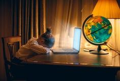 La muchacha consiguió dormida con el ordenador portátil en la noche Imágenes de archivo libres de regalías