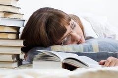 La muchacha consiguió cansada y se cayó lectura dormida un libro Imagen de archivo libre de regalías