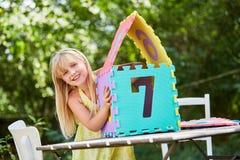 La muchacha construye una casa ideal fuera de pedazos del rompecabezas Fotos de archivo