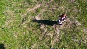 La muchacha corre con una cometa en un campo verde Risa y alegría, humor festivo D?a de fiesta de la familia metrajes
