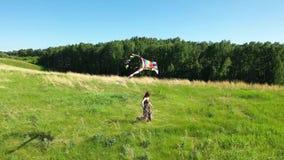 La muchacha corre con una cometa en un campo verde Risa y alegría, humor festivo Silla de cubierta en la playa en Brighton almacen de metraje de vídeo