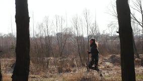 La muchacha corre en el bosque contra la perspectiva del sol almacen de metraje de vídeo