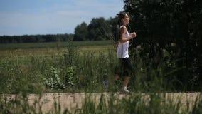 La muchacha corre en el camino en un campo almacen de metraje de vídeo