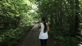 La muchacha corre en el camino en un campo almacen de video