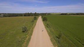 La muchacha corre en el camino en un campo Silueta del hombre de negocios Cowering almacen de metraje de vídeo