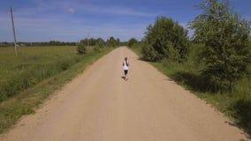 La muchacha corre en el camino en un campo Silueta del hombre de negocios Cowering almacen de video