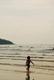La muchacha corre en el mar tiempo tan divertido y feliz Fotografía de archivo
