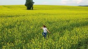 La muchacha corre en un campo de flor amarillo en la puesta del sol Cantidad del abej?n Entretenimiento al aire libre almacen de video