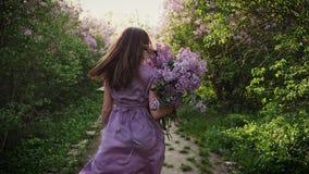 La muchacha corre junto con un ramo de lilas almacen de video