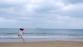 La muchacha corre a lo largo de la costa en la cámara lenta metrajes