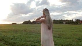 La muchacha corre a través del campo en la puesta del sol metrajes