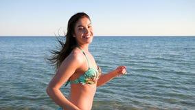 La muchacha corriente del retrato, las mujeres jovenes hermosas corre a lo largo de la playa contra el mar, cuerpo femenino en tr metrajes