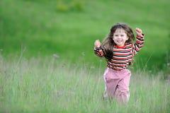 La muchacha corriente en un campo verde fotos de archivo