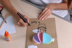 La muchacha corta con las tijeras, papel coloreado, sentándose en la tabla fotografía de archivo